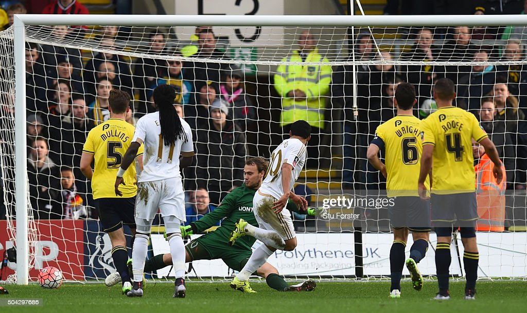 Jefferson Montero (C) of Swansea City scores the opening goal past Sam Slocombe of Oxford United during The Emirates FA Cup third round match between Oxford United and Swansea City at the Kassam Stadium on January 10, 2016 in Oxford, England.