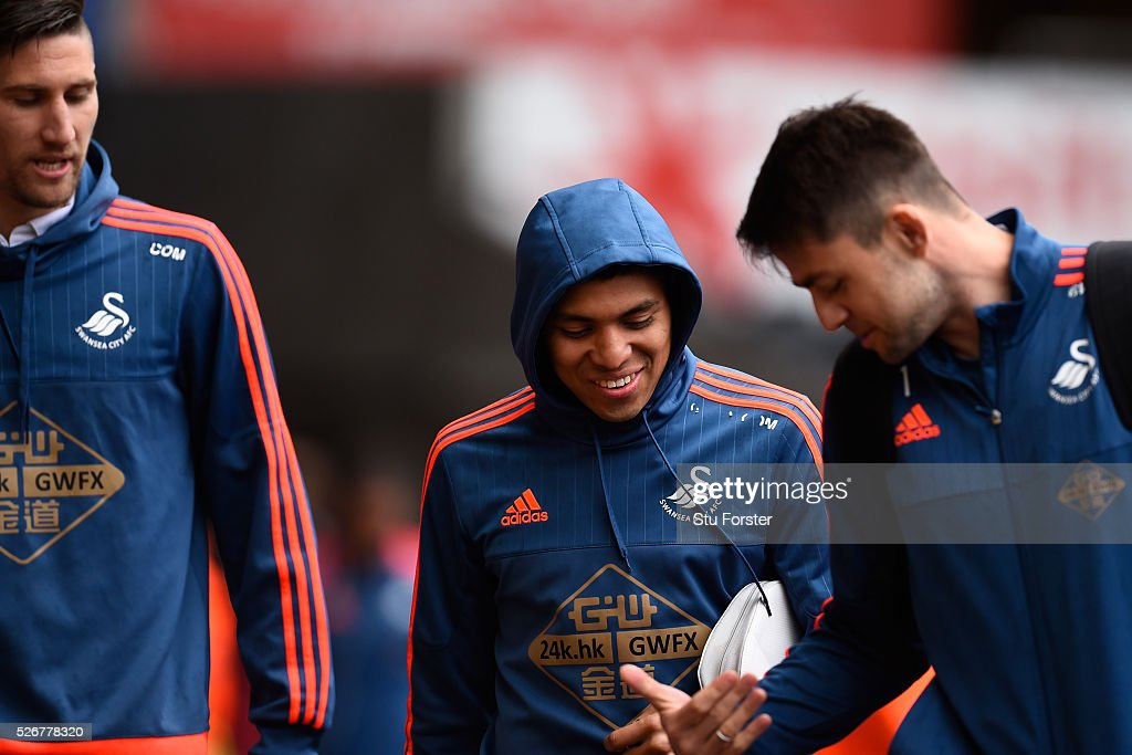 Jefferson Montero (C) of Swansea City talks with Lukasz Fabianski (R) as they arrive for the Barclays Premier League match between Swansea City and Liverpool at The Liberty Stadium on May 1, 2016 in Swansea, Wales.