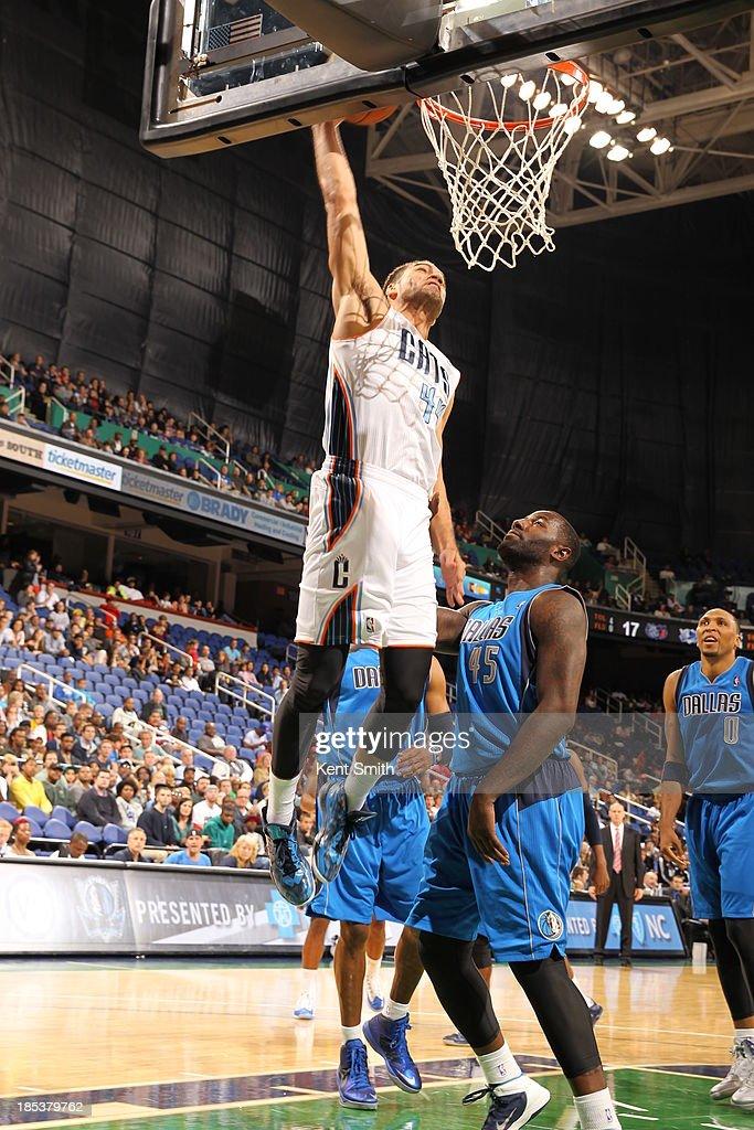 Jeffery Taylor #44 of the Charlotte Bobcats dunks against DeJuan Blair #45 of the Dallas Mavericks at the Greensboro Coliseum on October 19, 2013 in Greensboro, North Carolina.