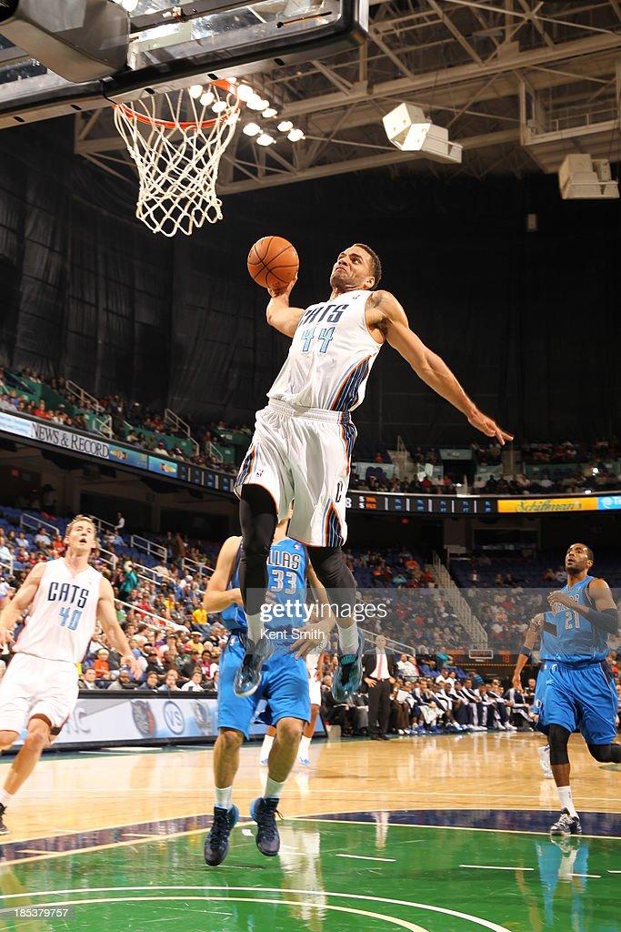 Jeffery Taylor #44 of the Charlotte Bobcats dunks against Gal Mekel #33 of the Dallas Mavericks at the Greensboro Coliseum on October 19, 2013 in Greensboro, North Carolina.
