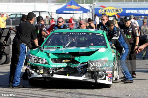Jeffrey Earnhardt's crew pushes their wrecked car to their hauler during the Monster Energy NASCAR Cup Series ISM Connect 300 race on September 24 at...
