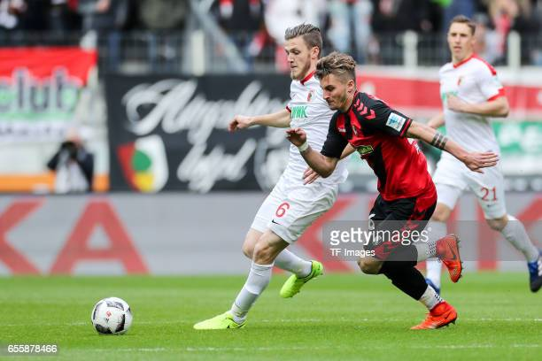 Jeffrey Gouweleeuw of Augsburg and Maximilian Philipp of Freiburg battle for the ball during the Bundesliga match between FC Augsburg and SC Freiburg...