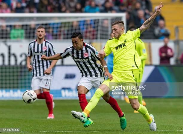 Jeffrey Gouweleeuw of Augsburg challenges Marco Fabian of Frankfurt during the Bundesliga match between Eintracht Frankfurt and FC Augsburg at...