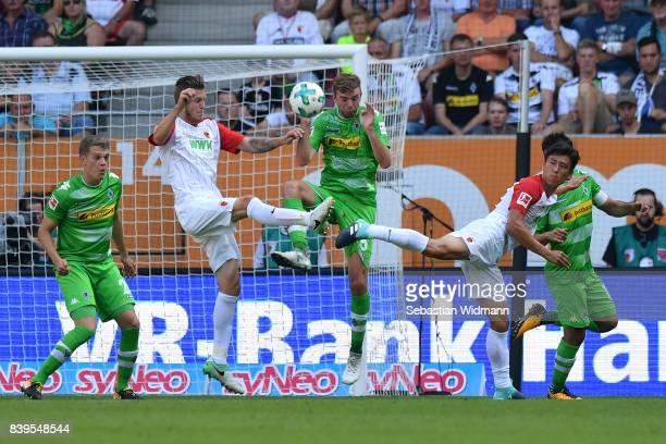 Jeffrey Gouweleeuw of Augsburg Christoph Kramer of Moenchengladbach and JaCheol Koo of Augsburg fight for the ball during the Bundesliga match...