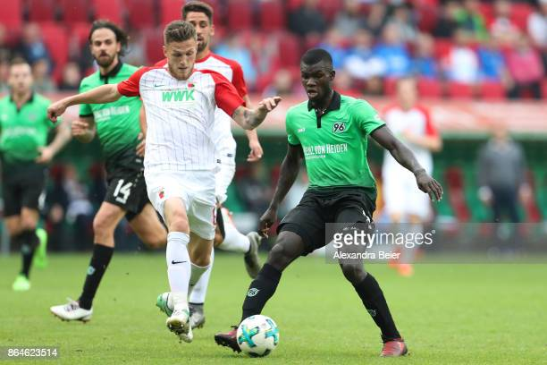 Jeffrey Gouweleeuw of Augsburg fights for the ball with Ihlas Bebou of Hannover during the Bundesliga match between FC Augsburg and Hannover 96 at...