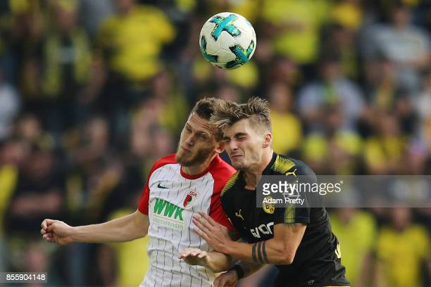 Jeffrey Gouweleeuw of Augsburg fights for the ball with Maximilian Philipp of Dortmund during the Bundesliga match between FC Augsburg and Borussia...