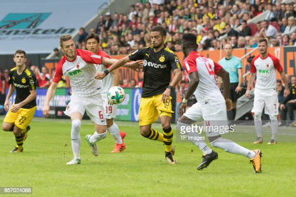 Jeffrey Gouweleeuw of Augsburg Jeremy Toljan of Dortmund Daniel Opare of Augsburg battle for the ball during the Bundesliga match between FC Augsburg...