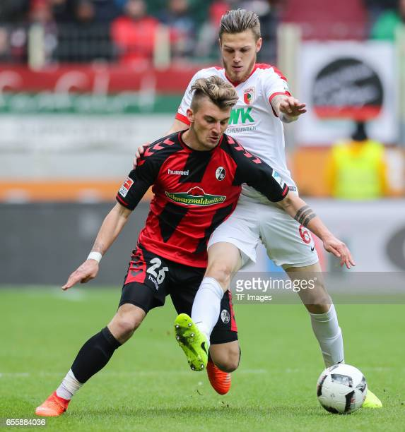Jeffrey Gouweleeuw of Augsburg Maximilian Philipp of Freiburg battle for the ball during the Bundesliga match between FC Augsburg and SC Freiburg at...