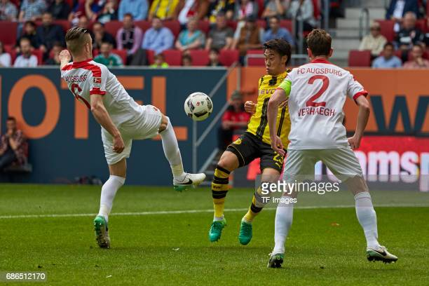 Jeffrey Gouweleeuw of Augsburg und Paul Verhaegh of Augsburg Shinji Kagawa of Dortmund battle for the ball during the Bundesliga match between FC...