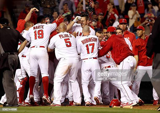 Jefry Marte Albert Pujols Shane Robinson congratulate CJ Cron of the Los Angeles Angels of Anaheim at home plate after Cron hit a walk off tworun...