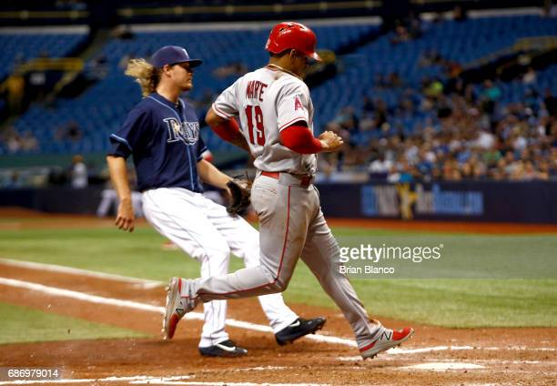 Jefry Marte of the Los Angeles Angels crosses home plate ahead of pitcher Ryne Stanek of the Tampa Bay Rays to score on a the wild pitch by Stanek...