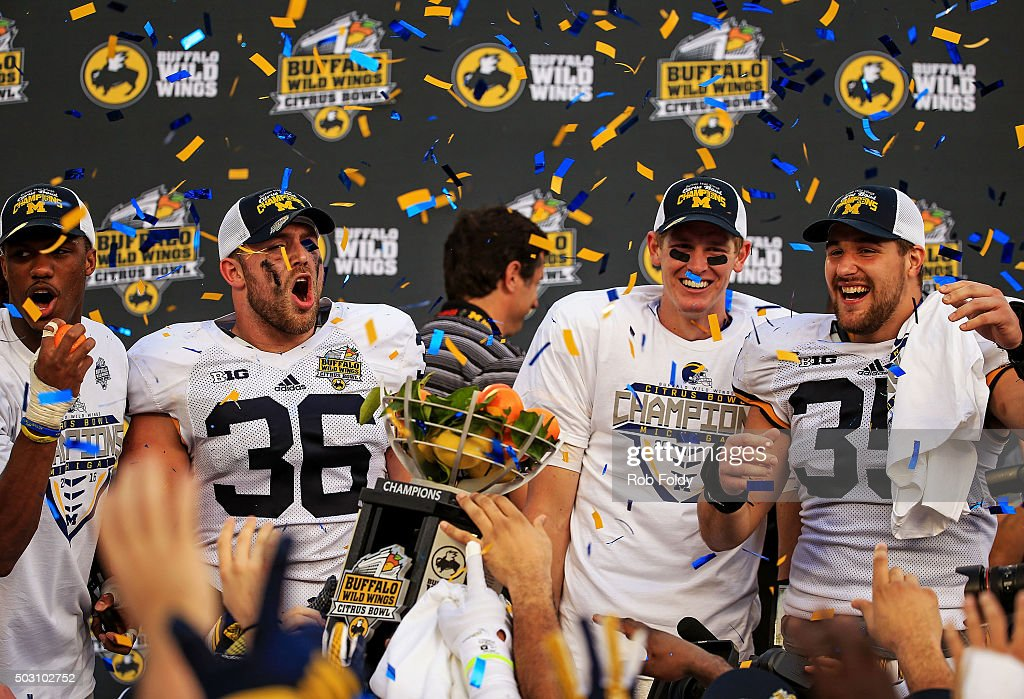 Jehu Chesson Joe Kerridge Joe Bolden and Jake Rudock of the Michigan Wolverines cheer after receiving the championship trophy after the Buffalo Wild...