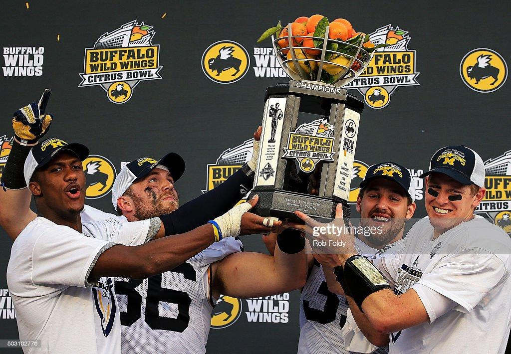 Jehu Chesson #86, Joe Kerridge #36, Joe Bolden #35 and Jake Rudock #15 of the Michigan Wolverines hold up the championship trophy after the Buffalo Wild Wings Citrus Bowl game against the Florida Gators at Orlando Citrus Bowl on January 1, 2016 in Orlando, Florida.