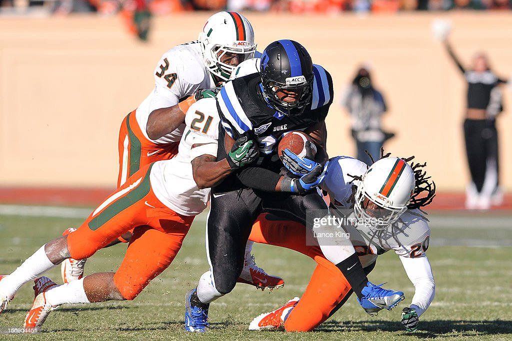 Jela Duncan #25 of the Duke Blue Devils runs against Brandon McGee #21 and Thomas Finnie #20 of the Miami Hurricanes at Wallace Wade Stadium on November 24, 2012 in Durham, North Carolina.