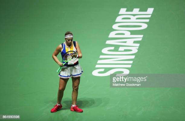 Jelena Ostapenko of Latvia adjusts her racquet between points while playing Garbine Muguruza of Spain during day 1 of the BNP Paribas WTA Finals...