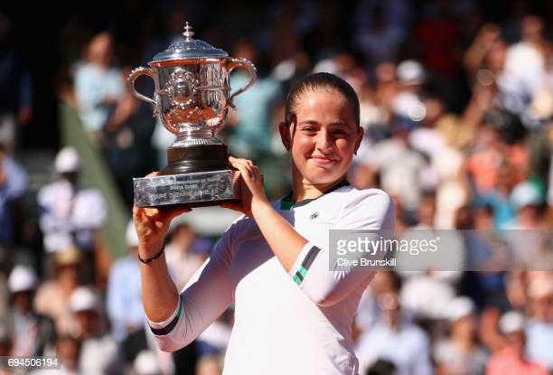 Jelena Ostapenko of Latvia celebrates victory with the trophy following the ladies singles final match against Simona Halep of Romania on day...