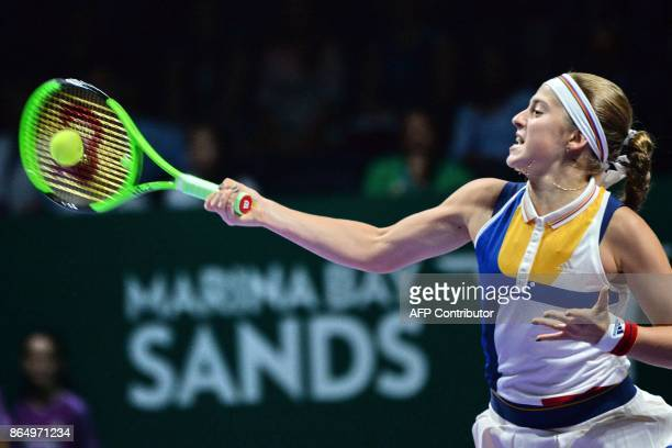 Jelena Ostapenko of Latvia hits a return against Garbine Muguruza of Spain during the WTA Finals tennis tournament in Singapore on October 22 2017 /...