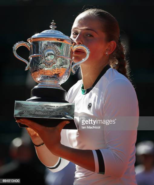 Jelena Ostapenko of Latvia poses with the trophy after her victory during her Women's Single Final match with imona Halep of Romania on day fourteen...