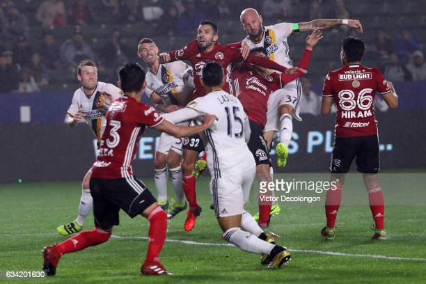 Jelle van Damme and Daniel Steres of the Los Angeles Galaxy vie for the corner kick with Jorge Alberto Ortiz of Club Tijuana during the first half of...