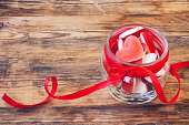 Jelly candy shape heart in glass jar with ribbon for Valentine's Day, closeup