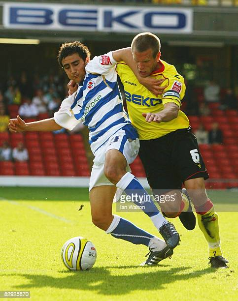 Jem Karacan of Reading holds off Jay DeMerit of Watford during the CocaCola Football League Championship match between Watford and Reading at...