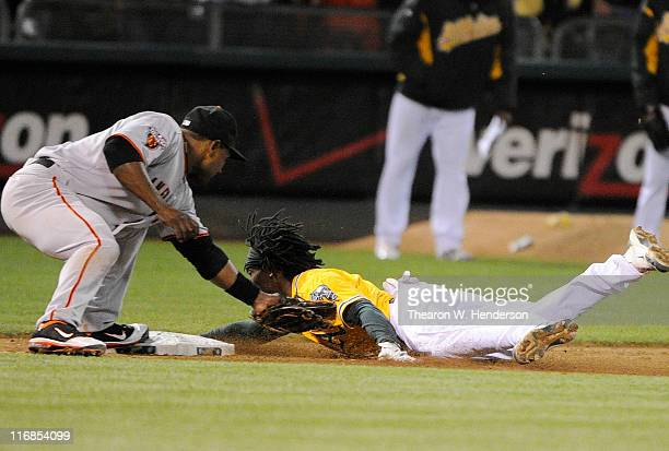 Jemile Weeks of the Oakland Athletics attempting to stretch a double into a triple is tagged out at third base by Miguel Tejada of the San Francisco...