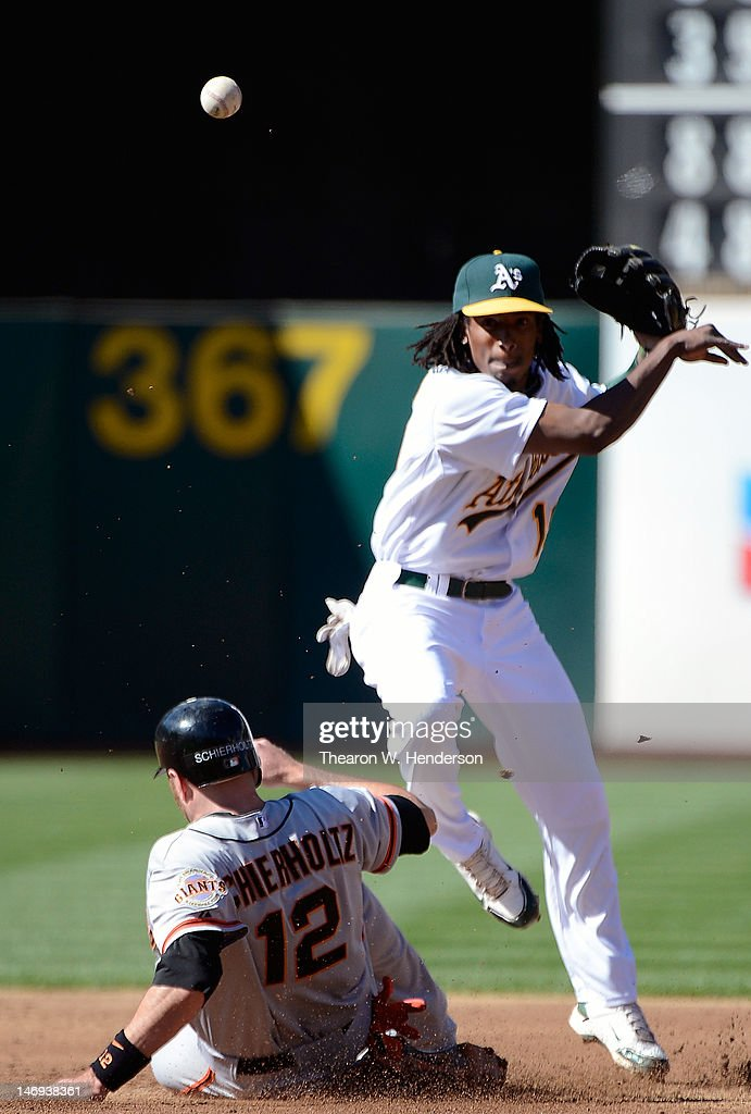 <a gi-track='captionPersonalityLinkClicked' href=/galleries/search?phrase=Jemile+Weeks&family=editorial&specificpeople=4583261 ng-click='$event.stopPropagation()'>Jemile Weeks</a> #19 of the Oakland Athletics gets his throw off to complete the double-play while avoiding the slide of <a gi-track='captionPersonalityLinkClicked' href=/galleries/search?phrase=Nate+Schierholtz&family=editorial&specificpeople=803208 ng-click='$event.stopPropagation()'>Nate Schierholtz</a> #12 of the San Francisco Giants in the second inning at O.co Coliseum on June 23, 2012 in Oakland, California.
