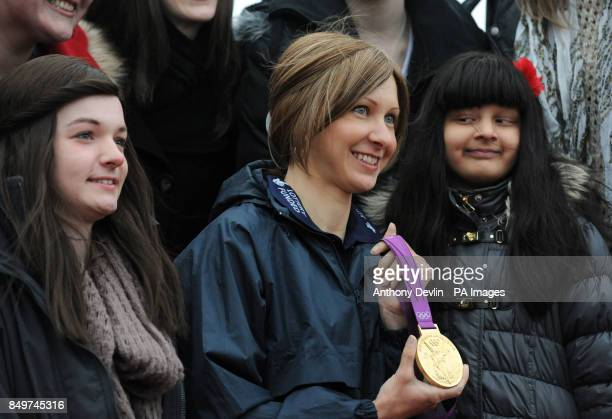 Jemma Graham 15 and Elina Batavia lookon as Olympic gold medalwinning cyclist Joanna Roswell shows off her gold medal as she meets members of the...