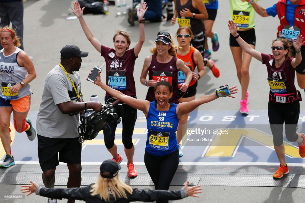 Colleen Hansen, center, triumphantly throws her arms out as she crosses the finish line in front of Kathrine Switzer, the first woman to run the Boston Marathon at the finish line of the 121st Boston Marathon in Boston on Apr. 17, 2017.