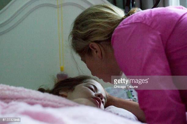 Jen VanHoutan gives her daughter Laine VanHoutan a goodnight kiss on June 20 in Downers Grove Ill