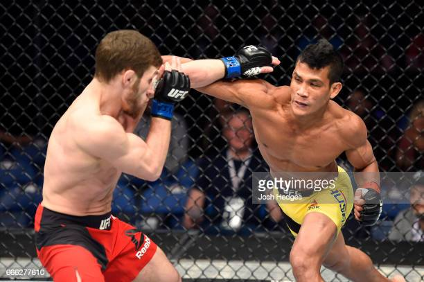 Jenel Lausa of the Philippines lands a punch on Magomed Bibulatov of Russia in their flyweight bout during the UFC 210 event at KeyBank Center on...