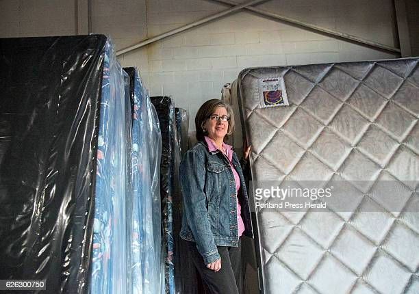 Jenn McAdoo executive director of Furniture Friends a nonprofit organization that provides furniture to people in need stands among box springs and...