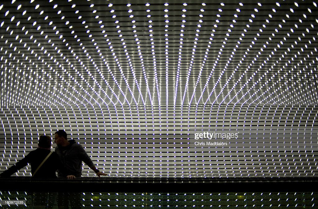Jenn Nadal and Derek Smith, from Ft. Lauderdale, Fl., ride the walkway in the National Gallery of Art through Leo Villareal's 'Multiverse,' the artist's largest and most complex light sculpture. The work features approximately 41,000 computer-programmed LED that run through channels along the 200-foot-long space.