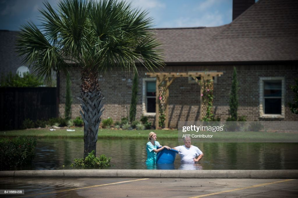 TOPSHOT - Jenna Fountain and her father Kevin carry a bucket down Regency Drive to try to recover items from their flooded home in Port Arthur, Texas, September 1, 2017. Storm-weary residents of Houston and other Texas cities began returning home to assess flood damage from Hurricane Harvey but officials warned the danger was far from over in parts of the battered state. / AFP PHOTO / Emily Kask