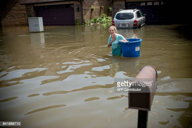 Jenna Fountain carries a bucket down flooded Regency Drive in Port Arthur Texas September 1 2017 Stormweary residents of Houston and other Texas...