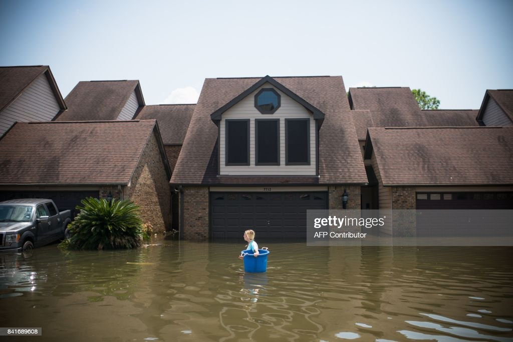 TOPSHOT - Jenna Fountain carries a bucket down Regency Drive to try to recover items from their flooded home in Port Arthur, Texas, September 1, 2017. Storm-weary residents of Houston and other Texas cities began returning home to assess flood damage from Hurricane Harvey but officials warned the danger was far from over in parts of the battered state. / AFP PHOTO / Emily Kask