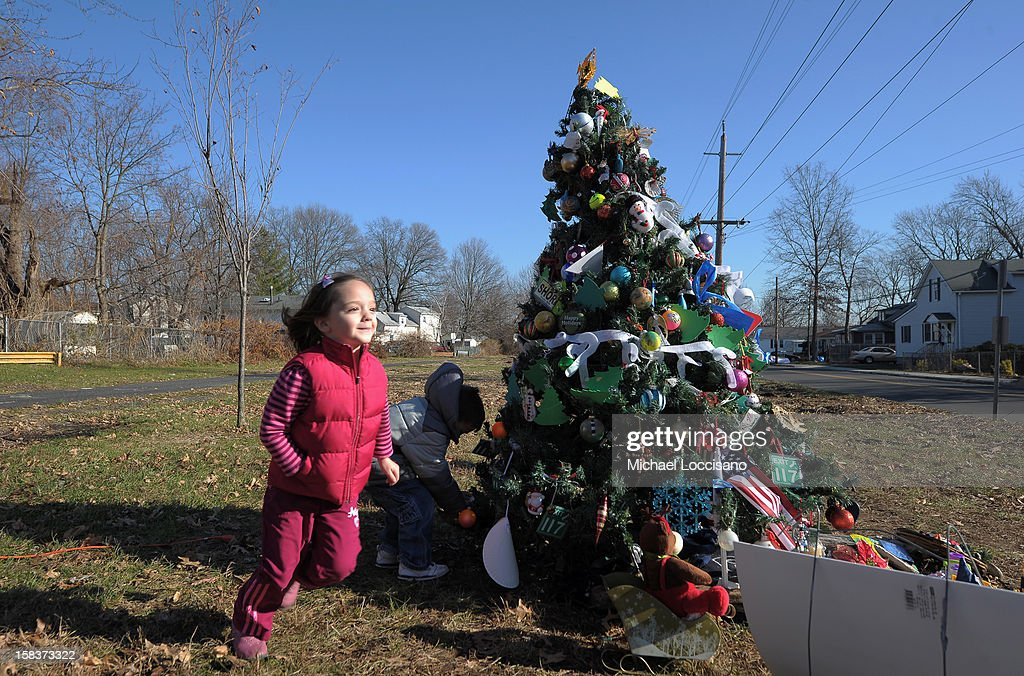 Jenna O'Brien (L) and John Covert visit an artificial Christmas tree, known as the 'Tree of Hope,' that stands in an empty grass lot on December 14, 2012 in Union Beach, New Jersey. The tree, rescued from a pile of trash and wreckage left by Superstorm Sandy and put up by a local resident, has been visited and decorated by people from all over who consider it a symbol of hope.