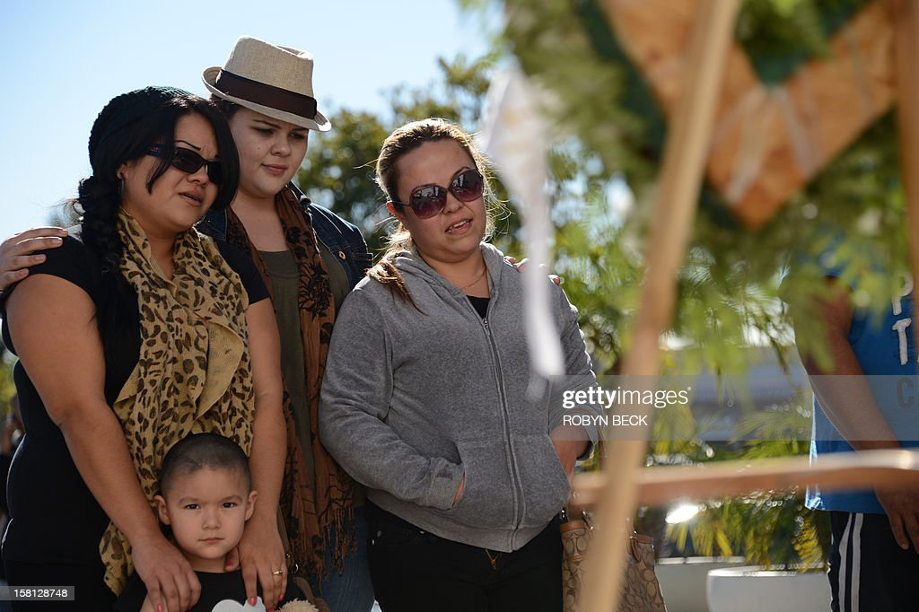 Jenni Rivera fan Ruby Montenegro (C) comforts fans Michelle Alonzo (L) and her neice Gaby Juarez at a memorial of flowers, candles, ballons and notes to the late Mexican-American singing superstar Jenni Rivera, December 10, 2012 in Burbank, California. Rescue workers searched Monday the wreckage of a plane that carried Rivera, a star on both sides of the border, whose death shocked Latin music fans and celebrities.