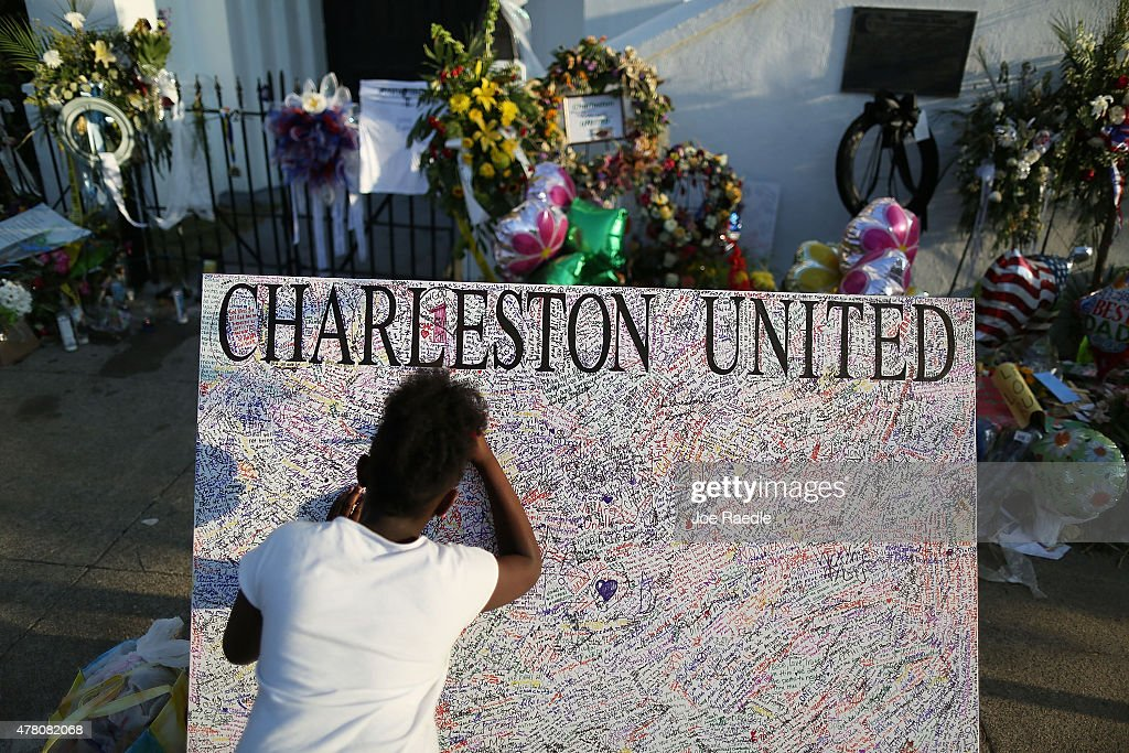 Jennice Barr, 10, leaves a message on a board set up in front of the Emanuel African Methodist Episcopal Church after a mass shooting at the church killed nine people, on June 22, 2015. 21-year-old Dylann Roof is suspected of killing nine people during a prayer meeting in the church in Charleston, which is one of the nation's oldest black churches.