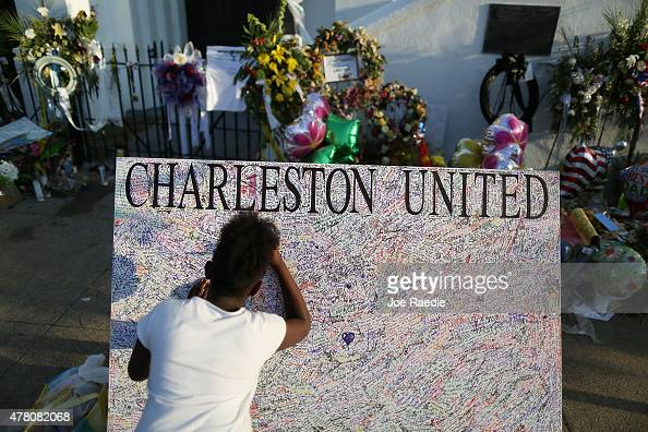 Jennice Barr leaves a message on a board set up in front of the Emanuel African Methodist Episcopal Church after a mass shooting at the church killed...