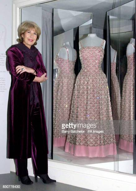 Jennie Bond Royal Correspondent for the BBC alongside one of the exhibits a pink silk organza evening dress designed by Hardy Amies and worn on seven...