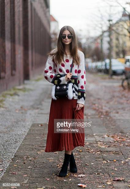 Jennifer Amanda wearing a colorful mohair sweater from Twin Set a pleated midi skirt from Baum und Pferdgarten in burtn henna black slimfitting ankle...