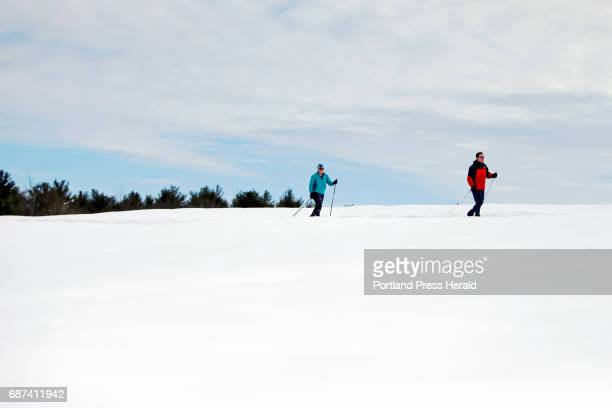 Jennifer and Adam Kozaryn of South Portland ski across an open meadow at Smiling Hill Farm on Saturday