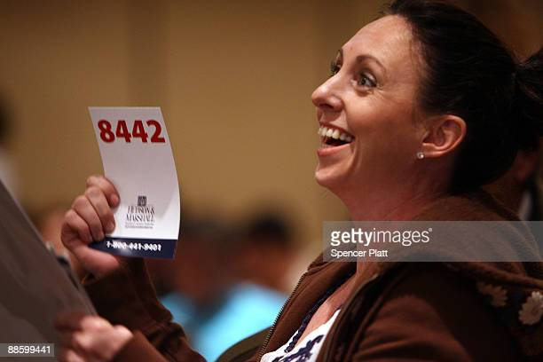 Jennifer Bernath successfully bids on a single family home during an auction for more than 25 foreclosed homes by auctioneers at Hudson Marshall at...