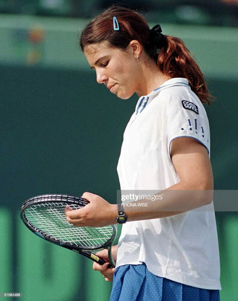 Jennifer Capriati of the US looks at her racquet a