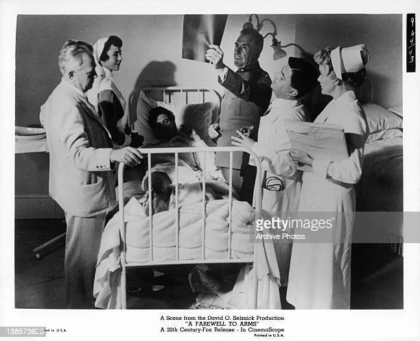 Jennifer Jones standing next to Rock Hudson as Victor Francen checks his XRay with Elaine Stritch standing by in a scene from the film 'A Farewell To...