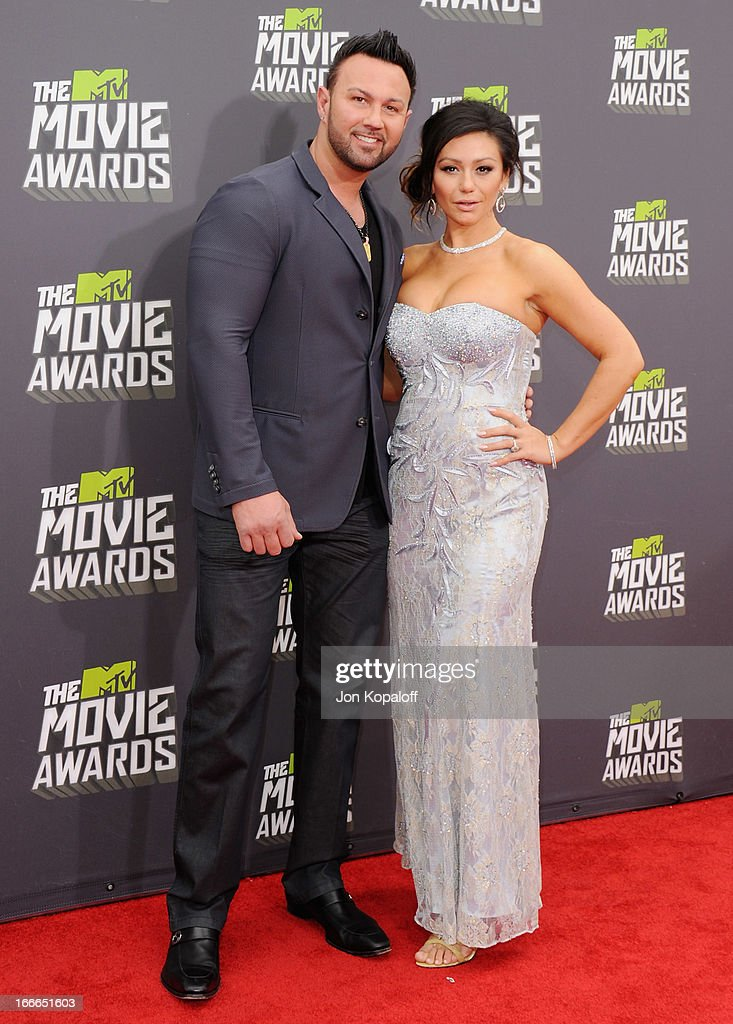 Jennifer 'JWoww' Farley and fiance Roger Mathews arrive at the 2013 MTV Movie Awards at Sony Pictures Studios on April 14, 2013 in Culver City, California.
