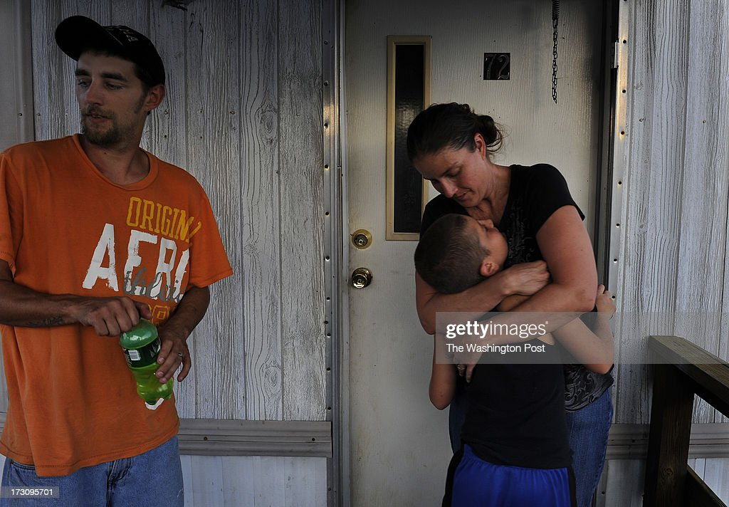 Jennifer Laughren is reunited with her son Anthony (age 9) after having not seen him for several days. He's been opting to stay with her mother on a nearby farm where it's less crowded and food is plentiful. At left is Jennifer's boyfriend Eric Jackson who's about to drink a Mountain Dew after doing some clean-up work around the trailer.Scores of poor children are served lunch each weekday in the areas around Greeneville, TN as 'The Lunch Express' bus visits trailer parks and housing developments in the summertime. Photo by Michael S. Williamson/The Washington Post via Getty Images