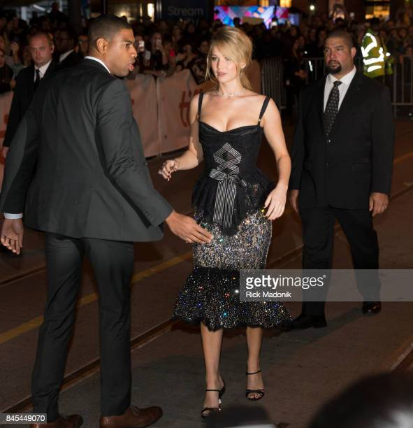 Jennifer Lawrence after signing autographs for fans is ushered back towards the entrance of the theatre TIFF red carpet outside Princess of Wales...