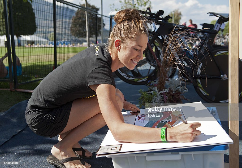 Jennifer Luebke of the United States signs an autograph during the Challenge Penticton Triathlon previews on August 24, 2013 in Penticton, British Columbia, Canada.